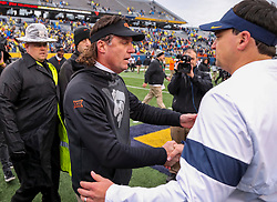 Nov 23, 2019; Morgantown, WV, USA; Oklahoma State Cowboys head coach Mike Gundy talks with West Virginia Mountaineers head coach Neal Brown after the game at Mountaineer Field at Milan Puskar Stadium. Mandatory Credit: Ben Queen-USA TODAY Sports