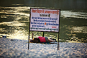 """A couple enjoying the sunset on the bank of River Ganga and the sign board reads, 'Welcome to the Boating area, Get your tickets for the motorboat from the counter only. You will be fined 10 times if found on the boat without the tickets. Please co-operate"""". . and last line says : Don't bathe here as the waters are too deep '"""