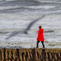 A women walk down the beach in Asbury Park during a storm that caused high surf to pound the coastline.