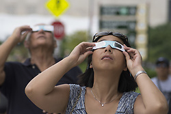 August 21, 2017 - Chicago, Illinois, USA - On August 21, 2017, the solar eclipse mesmerized people across the U.S. as the moon passed between the sun and earth.  In Chicago, thousands headed toward the Adler Planetarium by car, by bus or by walking. The Museum handed out 35,000  pairs of special eclipse glasses so that individuals could safely experience this once in a lifetime phenomenon.   The lakefront by the Planetarium also has one of the best views of the Chicago skyline.  At 1:19 PM, the coverage reached its peak in Chicago- not quite reaching totality, but still quite impressive. (Credit Image: © Karen I.Hirsch via ZUMA Wire)