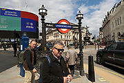 People outside the exit to Piccadilly Circus underground station on 25th May 2021 in London, United Kingdom. As the coronavirus lockdown continues its process of easing restrictions, more and more people are coming to the West End as more businesses open.