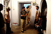 Members of the AVCC, (Anti-Violence Crime Cell) a special police unit mostly involved in anti-terrorism operations and kidnapping cases in the city of Karachi, are collecting their weapons from the AVCC armory in central Karachi in preparation of a night raid on the outskirts of the city searching for a kidnap suspect.