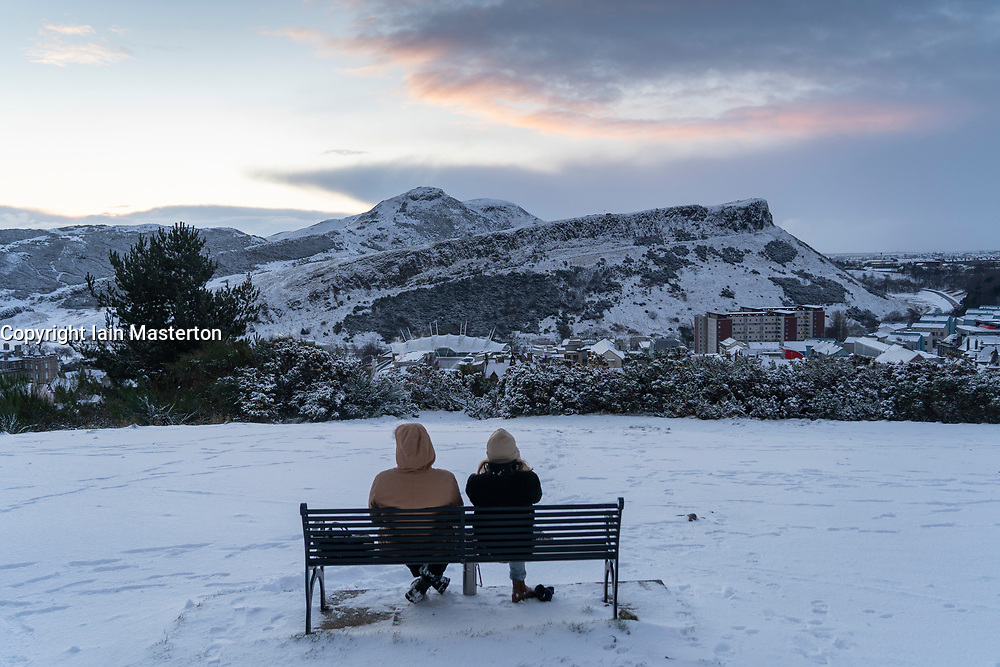 Edinburgh, Scotland, UK. 9 Feb 2021. Big freeze continues in the UK with Storm Darcy bringing several inches of snow to Edinburgh overnight. Pic; Couple watch sunrise over Salisbury Crags and Arthur's Seat. Iain Masterton/Alamy Live news