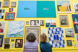 © Licensed to London News Pictures. 05/06/2018. LONDON, UK. Visitors views works at the preview of the 250th Summer Exhibition at the Royal Academy of Arts in Piccadilly, which has been co-ordinated by Grayson Perry RA this year.  Running concurrently, is The Great Spectacle, featuring highlights from the past 250 years.  Both shows run 12 June to 19 August 2018.  Photo credit: Stephen Chung/LNP