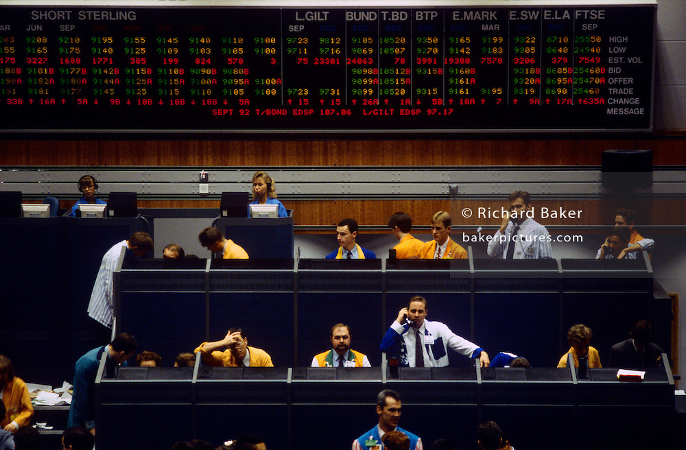 Brokers using the 'open cry' form of communicating futures and commodity prices on the trading floor at the London International Financial Futures Exchange (LIFFE) in the 1990s. The floor is also known as the bear pit where derivatives, options, futures and their contracts are exchanged in a frenzy of arm and hand expressions which communicate prices and quantities. The LIFFE exchange was synonymous with the Thatcherite capitalist money-making ethos in the City of London of the 80s and early 90s before the takeover by Euronext in January 2002. It is currently known as Euronext.liffe. Euronext subsequently merged with New York Stock Exchange in April 2007.
