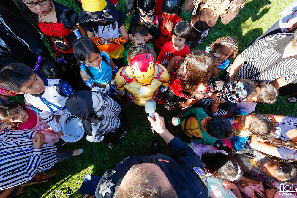 Children dressed in Halloween costumes surround Milpitas Police Officer Mark Doyle as he asks about their costumes during the annual Sunnyhills Neighborhood Association's Sunnyhills Pre-Halloween Party at Albert Augustine Jr. Memorial Park in Milpitas, California, on October 26, 2013. (Stan Olszewski/SOSKIphoto)