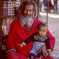 NEPAL, Kathmandu. Ascetic Hindu shopkeeper watches his grandchild near Pashupatinath Temple, Kathmandu, Nepal. Trident is a symbol of Shiva.