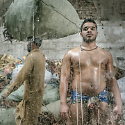 A Lahori pehlwan glistens with oil, applied via massage to aid in muscle relief.  Wrestlers practicing in Lahore - a traditional sport called Kuchti. Players are called Pehlwani.