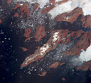 An image of icebergs off the west coast of Greenland, being transported by winds and currents. The largest iceberg in the image, seen in the top center of the image coming off of a glacier. July 17, 2005.