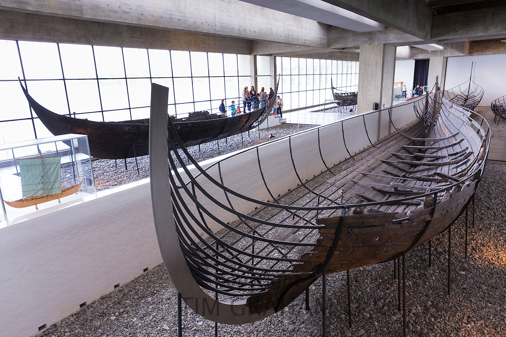 Tourists view Sculdelev original longboat exhibit at Roskilde Viking Ship Museum in Zealand, Denmark