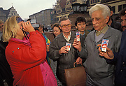 A year after the fall of the Berlin Wall and the end of the Communist Eastern Bloc, a cigarette brand marketing lady  hands out promos for Prince of Denmark and photographs unhappy-looking former east Germans with a Polaroid camera in Leipzigs town square, on 4th November 1990, in Leipzig, Germany.