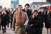 Commuters walk across London bridge to get to work in the City of London, UK. Thousands of commuters arrive into London Bridge station everyday and walk to work.