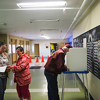041613  Adron Gardner/Independent<br /> <br /> Volunteer election worker Heather Trujillo, left, answers a question from Preciliana Schanefelt  as Perry Schanefelt, right, votes in the Gallup McKinley Schools Board of Education election at Gallup Middle School in Gallup Tuesday.