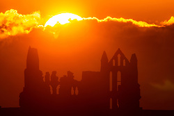 © Licensed to London News Pictures. 13/09/2021. Whitby UK. The sun rises over the gothic ruins of Whitby Abbey on the Yorkshire coast this morning as the UK heads towards a heatwave later this week. Photo credit: Andrew McCaren/LNP
