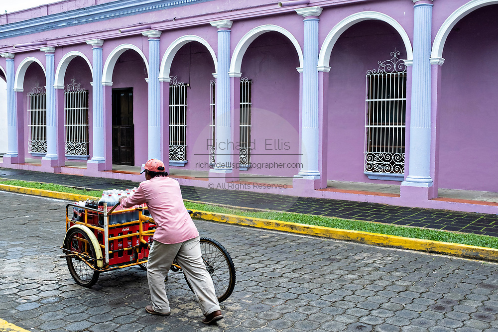 A tortilla vendor pushes his cargo bicycle past brightly painted colonnaded style homes in Tlacotalpan, Veracruz, Mexico. The tiny town is painted a riot of colors and features well preserved colonial Caribbean architectural style dating from the mid-16th-century.