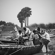 WHO's field volunteers load a motorbike onto a boat as they get ready to monitor inside embankment areas of the Kosi river at Alauli block, Khagaria, Bihar.