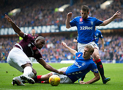 Hearts' Uche Ikpeazu (left) and Rangers Joe Worrall battle for the ball during the Ladbrokes Scottish Premiership match at Ibrox Stadium, Glasgow.