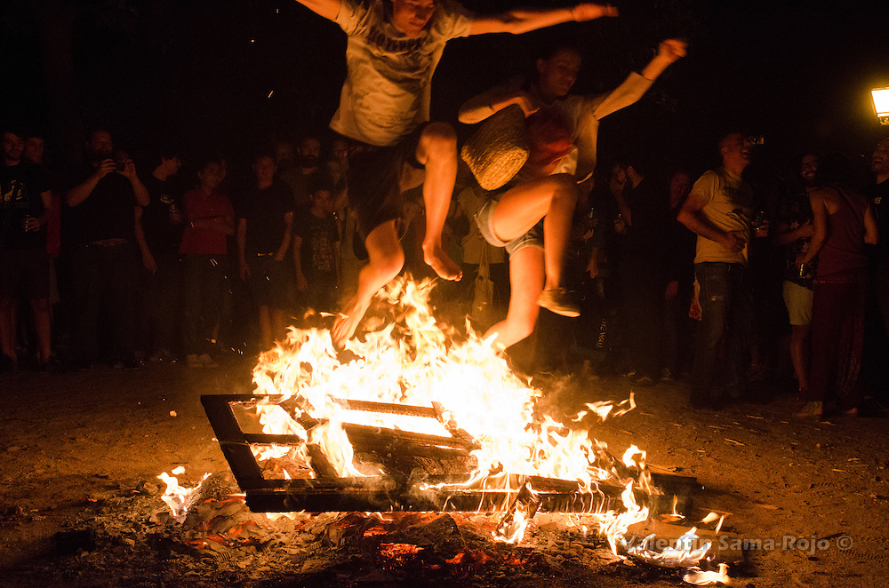 A couple jumping through the fire of a bonfire during Saint John's Eve in Madrid, the man jump barefeet.