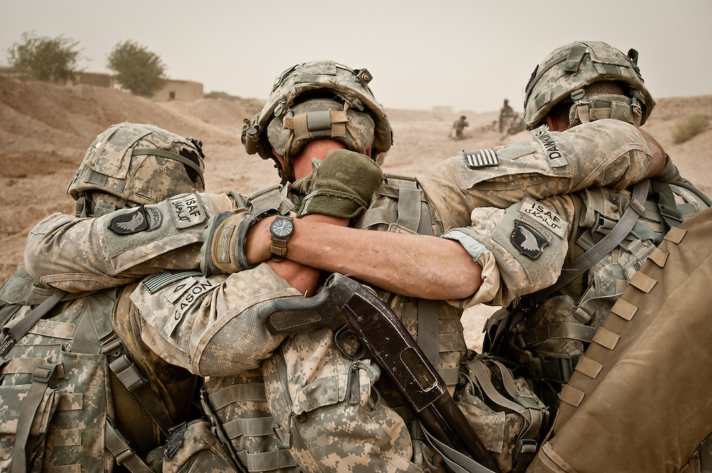 Soldiers escort a wounded comrade to a medevac site.