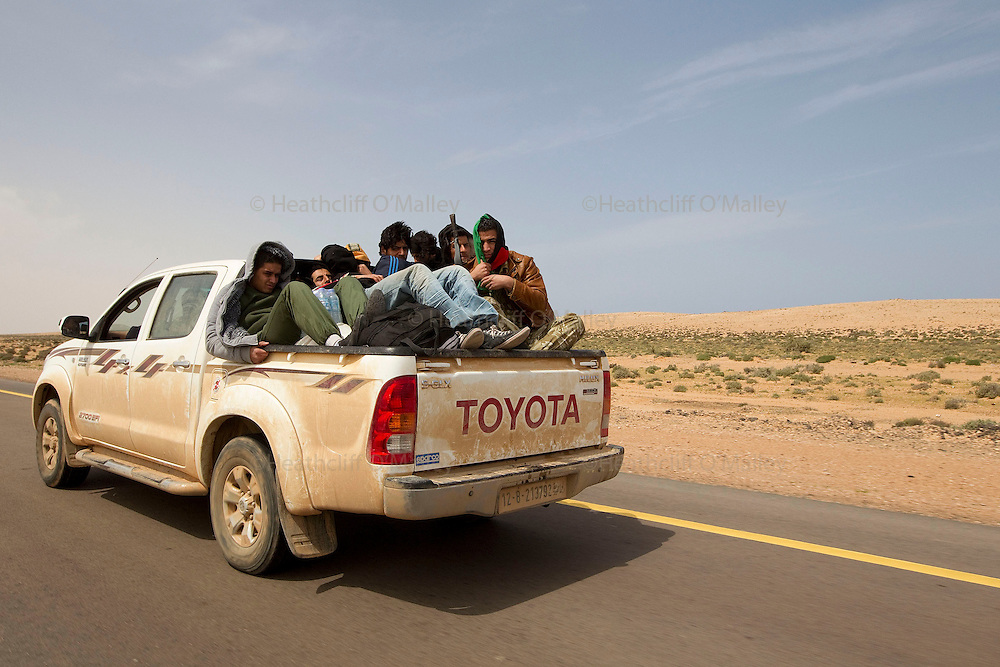 Mcc0030300 . Daily Telegraph..Libyan rebel volunteers in the back of a pick up truck.on their way up to a fluid frontline..Libyan government forces have been on forced retreat since saturday night due to repeated attacks from NATO airstrikes...Ras Lanuf 27 March 2011