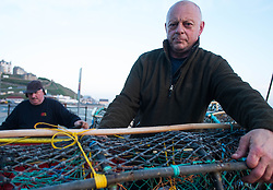 © Licensed to London News Pictures. <br /> 24/04/2015. <br /> <br /> Saltburn, United Kingdom<br /> <br /> Lesley Jefferson (R) stacks lobster pots on board the fishing boat Ellen before heading out to sea. The Ellen is the last remaining commercial fishing boat working out of Saltburn.<br /> <br /> <br /> Photo credit : Ian Forsyth/LNP