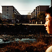Tieling city, Liaoning Province, China, 11-2003..A boy, whose mother works in Europe, stares at his home in China's northeastern rustbelt. The boy's mother arrived in Paris three years ago, and now works in a Chinese restaurant in Rotterdam. ..Millions of workers have been laid-off as China restructures its economy, slashing the bloated state-sector economy. .