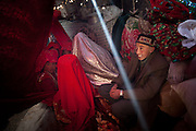 The new husband stands beside his wife..At the camp of Tash Seri (Mustafa Qol's camp). Ikhbal, 15, wearing a white veil,  is kept hidden being a large red cloth, inside a yurt, where she will stay for a few days. She will sleep here, be fed here etc..With Ikhbal, the recently married woman  moving for the first time to her husband's camp..She just exchanged the red veil of the unmarried girl for the white veil signifying that she is now a married woman...Trekking through the high altitude plateau of the Little Pamir mountains, where the Afghan Kyrgyz community live all year, on the borders of China, Tajikistan and Pakistan.