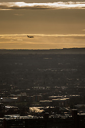 © Licensed to London News Pictures . 07/12/2013 . View over south Manchester with an aeroplane coming in to land at Manchester Airport . Cityscape view of Manchester . Photo credit : Joel Goodman/LNP