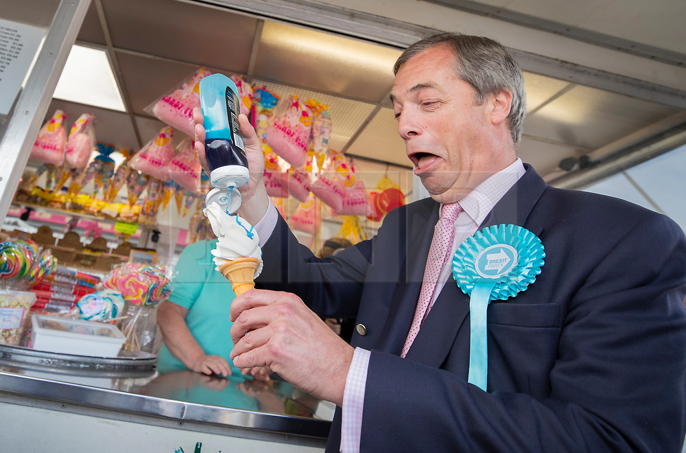 © Licensed to London News Pictures. 18/05/2019. Canvey Island, UK. Brexit Party leader Nigel Farage pours an appropriately coloured syrup on his ice cream as he campaigns for the European Elections in Canvey Island, Essex. The European Elections are being held on Thursday 23rd May. Photo credit: Peter Macdiarmid/LNP