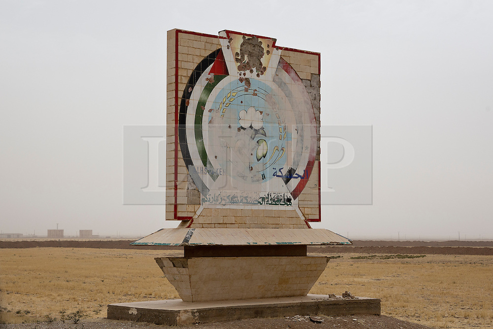 © Licensed to London News Pictures. 28/09/2014. Al-Yarubiyah, Syria. Pock marked by bullets, a sign thanking people for visiting Syria's Hasakah Governate is seen on the outskirts of the Syrian border town of Al-Yarubiyah.<br /> <br /> Facing each other across the Iraq-Syria border, the towns of Al-Yarubiyah, Syria, and Rabia, Iraq, were taken by Islamic State insurgents in August 2014. Since then The town of Al-Yarubiyah and parts of Rabia have been re-taken by fighters from the Syrian Kurdish YPG. At present the situation in the towns is static, but with large exchanges of sniper and heavy machine gun fire as well as mortars and rocket propelled grenades, recently occasional close quarter fighting has taken place as either side tests the defences of the other. Photo credit: Matt Cetti-Roberts/LNP