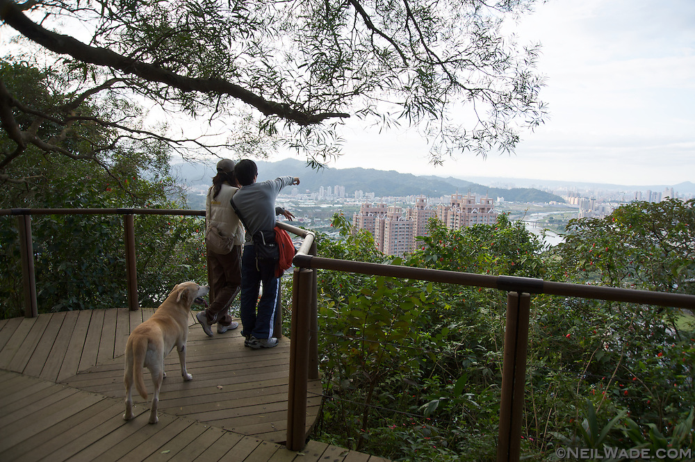 A couple and their dog view Xindian (Taipei), Taiwan from a hiking trail.
