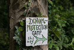 A sign placed by activists from HS2 Rebellion in Colne Valley Park indicates the path to the Denham protection camp on 26th June 2020 in Denham, United Kingdom. Activists from HS2 Rebellion and Extinction Rebellion UK are taking part in a 'Rebel Trail' hike along the route of the HS2 high-speed rail link in protest against its environmental impact and to question the viability of the £100bn+ project.