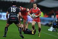 Gareth Davies of the Scarlets goes past Dan Evans (15) and Jeff Hassler (on ground)  of the Ospreys to set up the 1st half try from DTH Van Der Merwe of Scarlets. Guinness Pro12 rugby match, Ospreys v Scarlets at the Liberty Stadium in Swansea, South Wales on Saturday 26th March 2016.<br /> pic by  Andrew Orchard, Andrew Orchard sports photography.