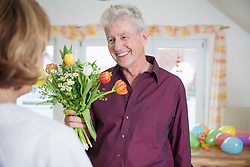 Senior man hand over bouquet to woman on birthday, smiling
