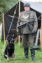 A Re-enactor portraying a German Feldgendarme from the elite German Heer Panzer Grenadier Division Großdeutschland with Alsatian dog and carrying a MP40 machine pistol. during a battle battle re-enactment in on Pickering Showground<br />