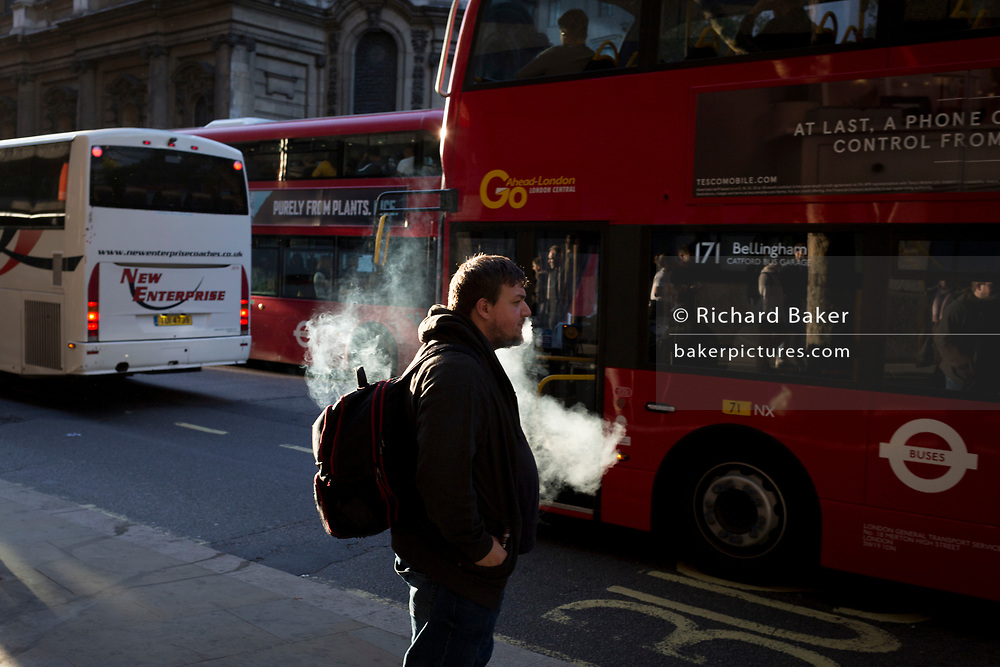 A vaper exhales before boarding a bus during the evening rush-hour in the capital, on 3rd October 2018, in London, England.