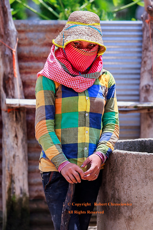 Cutie: A young woman construction worker, somehow able to work in the excessive tropical heat while protected from the sun by being fully clothed, peaks out from her hat and scarf revealing an angelic look, Battambang Cambodia.