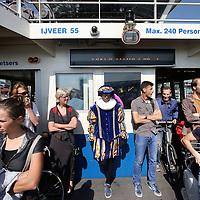 Nederland, Amsterdam , 3 juli 2014.<br /> Zwarte Piet aan boord van het pontje tussen Centraal Station en de Buiksloterweg in Amsterdam Noord.<br /> De Gemeente Amsterdam moet het besluit over de vergunning voor de Sinterklaasintocht van vorig jaar herzien, omdat de belangen van tegenstanders van Zwarte Piet niet goed afgewogen zijn.<br /> De discussie laait weer op.<br /> Foto:Jean-Pierre Jans