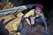 Gold mine in South Kivu, DRC Congo. A miner hauls a bag of ore through the shaft tunnel he works. Above his head runs an oxigen supply hose that is supposed to prevent asphyxiation. Murale, South Kivu, DRC. August 21, 2010.<br /> Un creuseur monte un lourd sac de minerai d'or à travers le tunnel de la mine. Au-dessus de sa tête court un tuyau d'alimentation en oxygène censé empêcher l'asphyxie. Murale, Sud-Kivu, RDC. 21 août 2010.