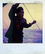 Old polaroid of a young fisherman standing on a boat holding a taught rope for support looking into the distance, Palawan Island, Philippines, Southeast Asia