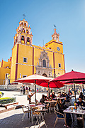 People in an outdoor cafe by the Baroque style, Parroquia de Basílica Colegiata de Nuestra Señora de Guanajuato or Guanajuato Basilica in the historic center of Guanajuato City, Guanajuato, Mexico. The massive basilica is painted bright yellow, located in along the Plaza of Peace and was built in 1671.