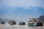 Tourist boats travel along Li River between Guilin and Yangshuo, China