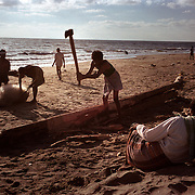 A fisherman chops a boat laid waste by the tsunami on a beach in Nagappattinam, on the southeastern coast of India. .The December 26, 2004 tsunami killed thousands of people along this coast, smashing boats, roads and houses and tearing thousands of families apart. .Picture taken February 2005 in Nagapptinam, Tamil Nadu, India, by Justin Jin