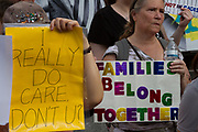 """People holding signs reading """"I really do care"""" take part in the families Belong Together Rally to protest the policy of separating migrant families as they cross the Southern US border carried out by the Administration of President Donald Trump in Tokyo's iconic Hachiko Square in Shibuya, Japan. Saturday June 30th 2018. Around thirty people from Democrats Abroad Japan, along with Japanese and other foreigners, took part in the demo which was part of an international day of action that saw more than 625 protests worldwide."""