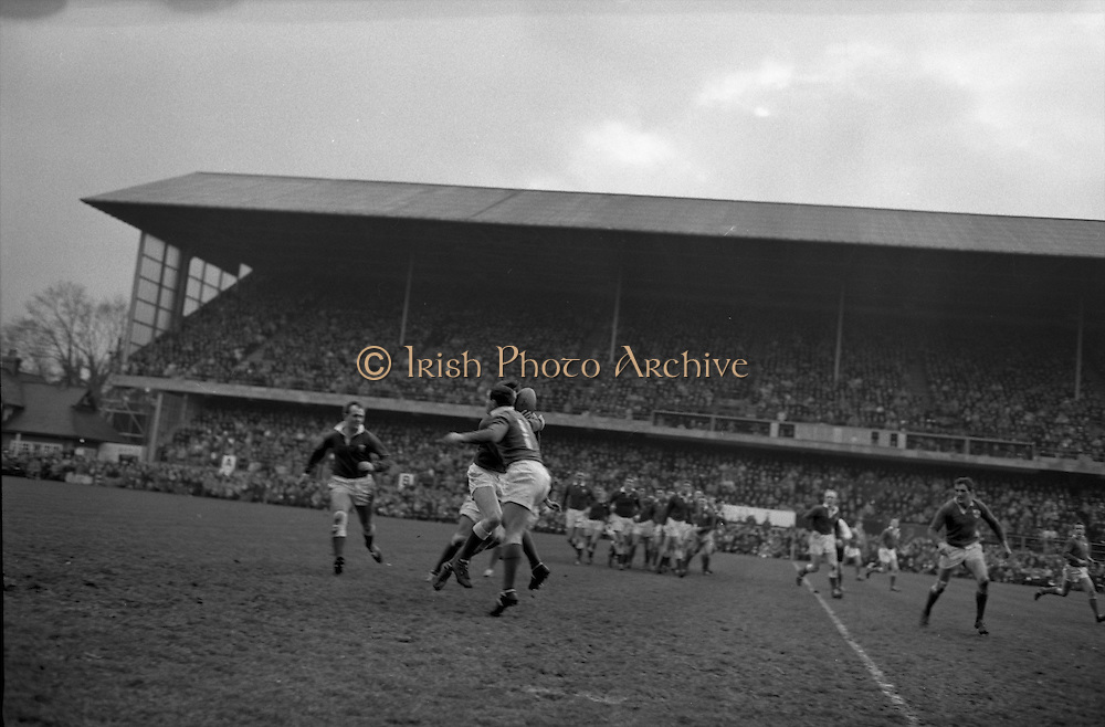 Houston, number 11, tackles Welsh back in possession, ..Irish Rugby Football Union, Ireland v Wales, Five Nations, Landsdowne Road, Dublin, Ireland, Saturday 7th March, 1964,.7.3.1964, 7.3.1964,..Referee- A C Luff, Rugby Football Union, ..Score- Ireland 6 - 15 Wales, ..Irish Team, ..F S Keogh, Wearing  Number 15 Irish jersey, Full Back, Bective Rangers Rugby Football Club, Dublin, Ireland,  ..P J Casey, Wearing number 14 Irish jersey, Right Wing, University College Dublin Rugby Football Club, Dublin, Ireland, .. M K Flynn, Wearing number 13 Irish jersey, Right Centre, Wanderers Rugby Football Club, Dublin, Ireland, ..J C Walsh,  Wearing number 12 Irish jersey, Left Centre, University college Cork Rugby Football Club, Cork, Ireland,..K J Houston, Wearing number 11 Irish jersey, Left Wing, Queens University Rugby Football Club, Belfast, Northern Ireland,..C M H Gibson, Wearing number 10 Irish jersey, Stand Off, Cambridge University Rugby Football Club, Cambridge, England, and, N.I.F.C, Rugby Football Club, Belfast, Northern Ireland, ..J C Kelly, Wearing number 9 Irish jersey, Scrum Half, University College Dublin Rugby Football Club, Dublin, Ireland,..P J Dwyer, Wearing number 1 Irish jersey, Forward, University College Dublin Rugby Football Club, Dublin, Ireland, ..P Lane, Wearing number 2 Irish jersey, Forward, Old Crescent Rugby Football Club, Limerick, Ireland, ..T A Moroney, Wearing number 3 Irish jersey, Forward, University College Dublin Rugby Football Club, Dublin, Ireland, ..W A Mulcahy, Wearing number 4 Irish jersey, Captain of the Irish team, Forward, Bective Rangers Rugby Football Club, Dublin, Ireland,  ..M W Leahy,  Wearing number 5 Irish jersey, Forward, University college Cork Rugby Football Club, Cork, Ireland,..E P McGuire,  Wearing number 6 Irish jersey, Forward, University college Galway Rugby Football Club, Galway, Ireland,..M G Culliton, Wearing number 8 Irish jersey, Forward, Wanderers Rugby Football Club, Dublin, Ireland, ..N A Murphy, Wearing