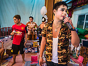 "30 JANUARY 2016 - NONTHABURI, NONTHABURI, THAILAND: A performer warms up by singing to the crowd from backstage before a ""likay"" show at Wat Bua Khwan in Nonthaburi, north of Bangkok. Likay is a form of popular folk theatre that includes exposition, singing and dancing in Thailand. It uses a combination of extravagant costumes and minimally equipped stages. Intentionally vague storylines means performances rely on actors' skills of improvisation. Like better the known Chinese Opera, which it resembles, Likay is performed mostly at temple fairs and privately sponsored events, especially in rural areas. Likay operas are televised and there is a market for bootleg likay videos and live performance of likay is becoming more rare.     PHOTO BY JACK KURTZ"