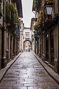 Typical street scene of narrow alleyway in quaint town of Guimaraes in Northern Portugal