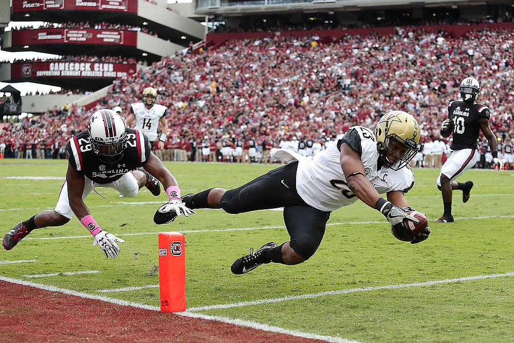 Vanderbilt's Khari Blasingame (23) dives past South Carolina's Antoine Wilder (29) for a touchdown in the first quarter of the game. <br /> Vanderbilt Commodores vs. South Carolina Gamecocks at Williams-Brice Stadium in Columbia, S.C. on Saturday, Oct. 28, 2017.<br /> Zach Bland/Vanderbilt Athletics
