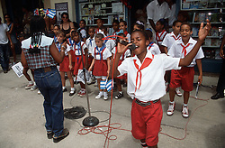Young boy wearing uniform singing into microphone on Havana street at World Book Day event with other school children accompanying him,