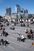 People enjoying some sunny weather socialising at The Scoop at More London and overlooking the cityscape and skyline of the City of London financial district on 17th April 2021 in London, United Kingdom.